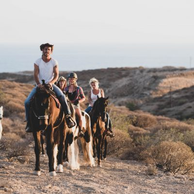group of people riding on a horse together walking and discovering new places