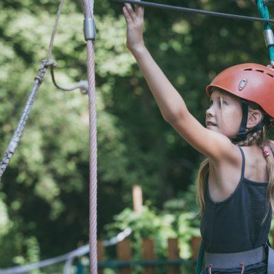 little girl make climbing in the adventure park.