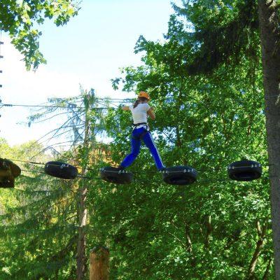 Woman walking on suspended wire-bridge in an adventure park